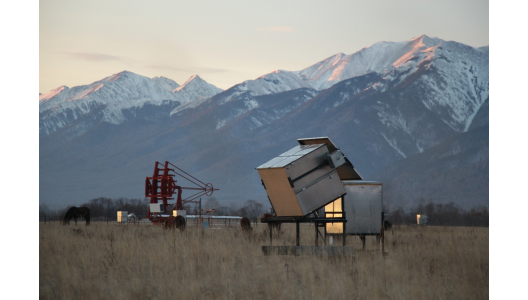 A HiSCORE station with its electronics box in the foreground and an IACT under construction in the background, located in the Tunka valley in Siberia. Credit: Taiga Collaboration.