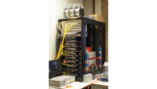 Figure 1. Timing System Setup in Amsterdam. It consists of several White Rabbit Switches from Seven Solutions (top panels in the rack), a copper ethernet switch, an Arbiter 1084B GPS, 32x ZEN-CTA boards (four in each of the lower panels of the rack) and several kilometers of single-mode optical fibers (e.g., on top of the rack).Image credit: Heike Prokoph.